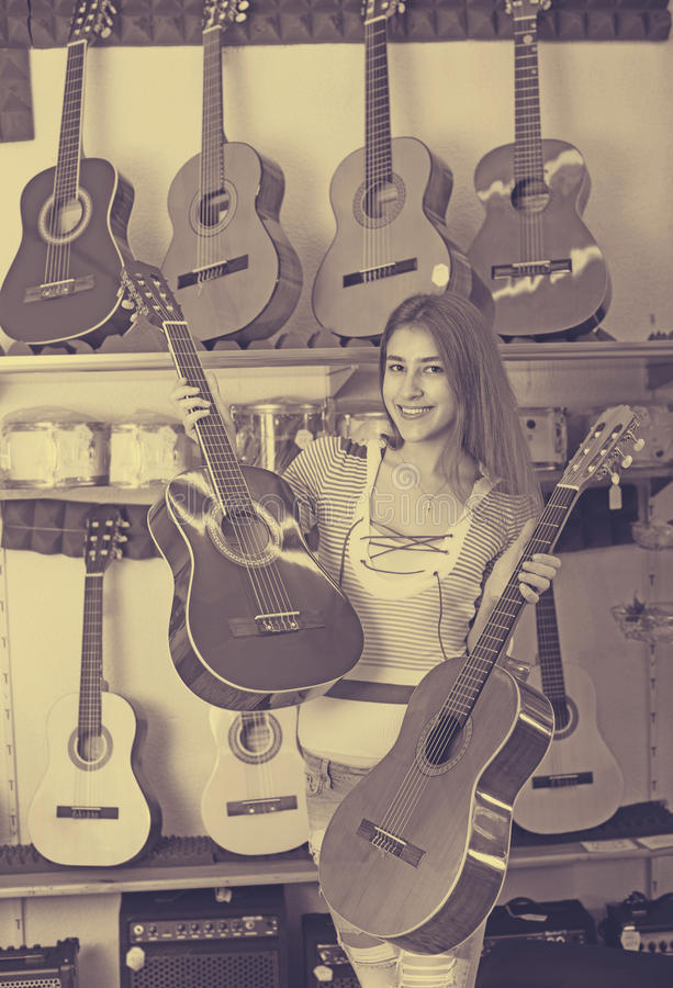 Girl choosing acoustic guitar. Brunette girl choosing acoustic guitar in music instruments shop indoors royalty free stock image