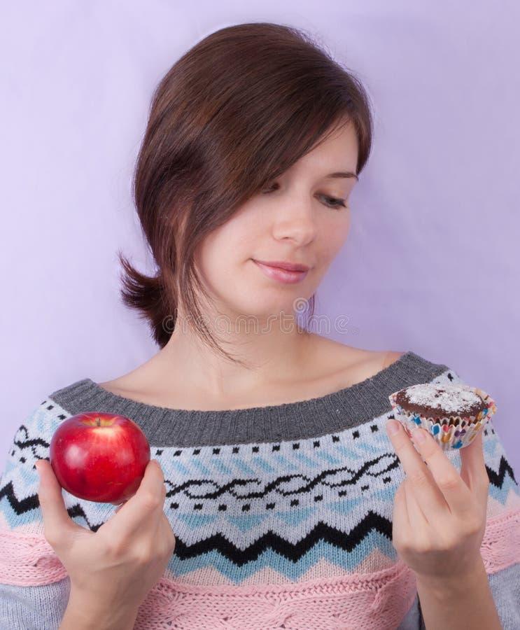 Girl choosing between apple and cupcake stock photos