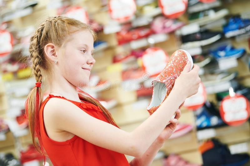 Season sale. Little girl shopping walking shoe. Girl choosing footwear during shopping at garments apparel shoe shop. Season sale stock photos