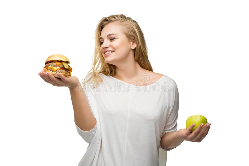 Girl in choosing the right food. A young woman in a difficult choice of food for her health royalty free stock images