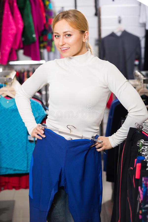 Girl choosing a trousers in sport store. Smiling blonde girl choosing and fitting new fitness pants in the sport store royalty free stock photo