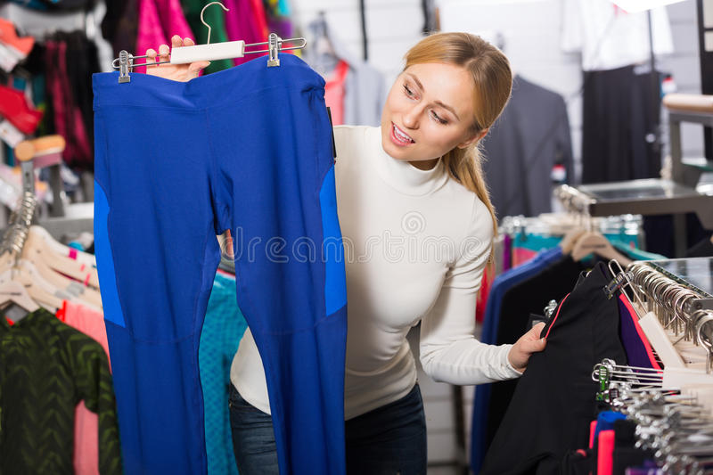 Girl choosing a trousers in sport store stock images