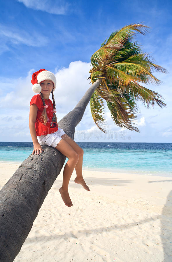 Download Girl In Christmas Hat Sitting On A Palm Stock Image - Image: 17266003