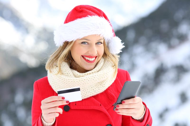 Girl on christmas holding credit card and phone. Happy girl on christmas wearing santa claus hat holding credit card and smart phone with a snowy mountain in the royalty free stock photography