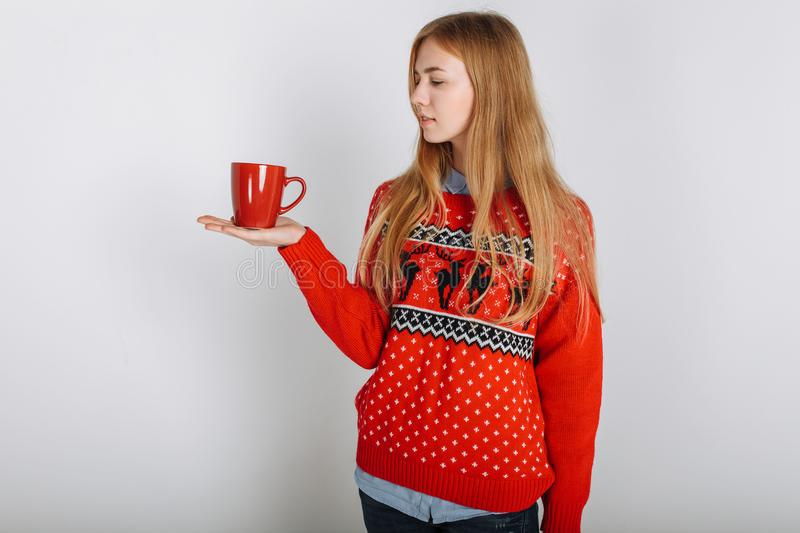 Girl in a Christmas or new year sweater in the Studio holding a Cup of flavored coffee. place for text Christmas mood. High quality photo royalty free stock photos