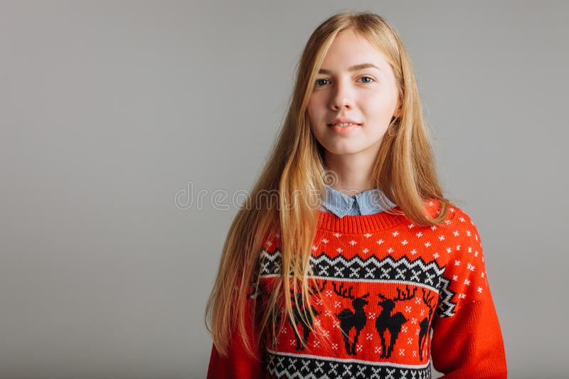 Girl in a Christmas or new year sweater in the Studio holding a Cup of flavored coffee. place for text Christmas mood. Girl in a Christmas or new year sweater royalty free stock image