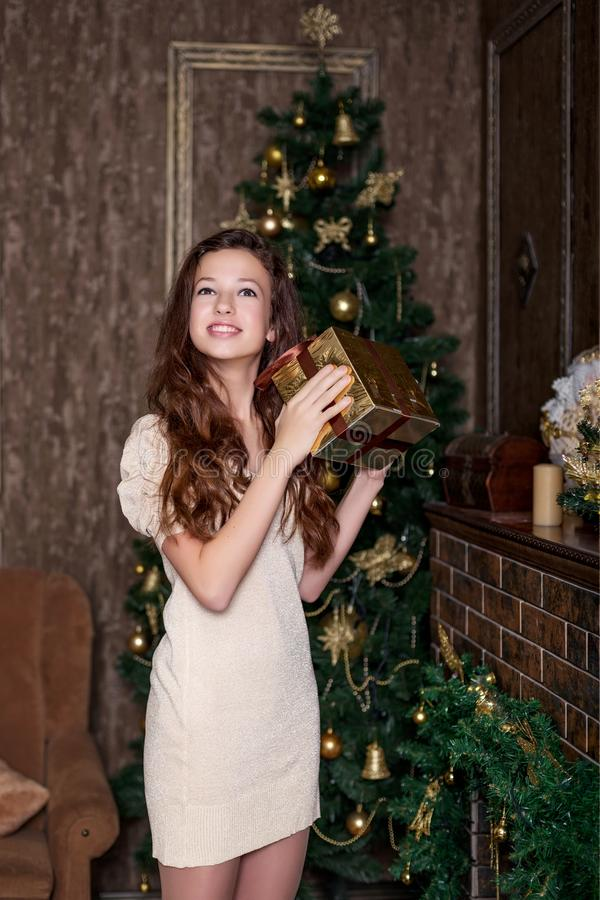 Cute girl with a christmas present in hands in delight happy standing in the living room of a classic style in a gold retro vintag royalty free stock photography