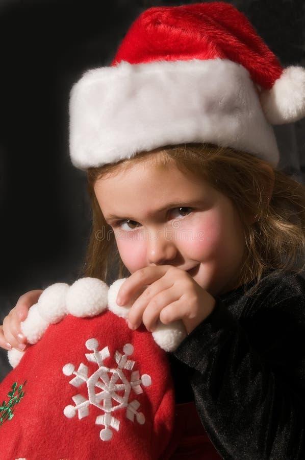 Girl with Christmas stocking. Cute preschool girl in Santa Claus hat looking in Christmas stocking, black background stock photos