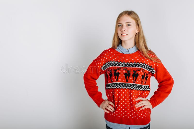 Girl in a Christmas sweater. Holiday Christmas. Christmas sweater. Beautiful girl holding a red Cup. The Christmas cheer.Christmas sweater. Photo to insert text royalty free stock photography