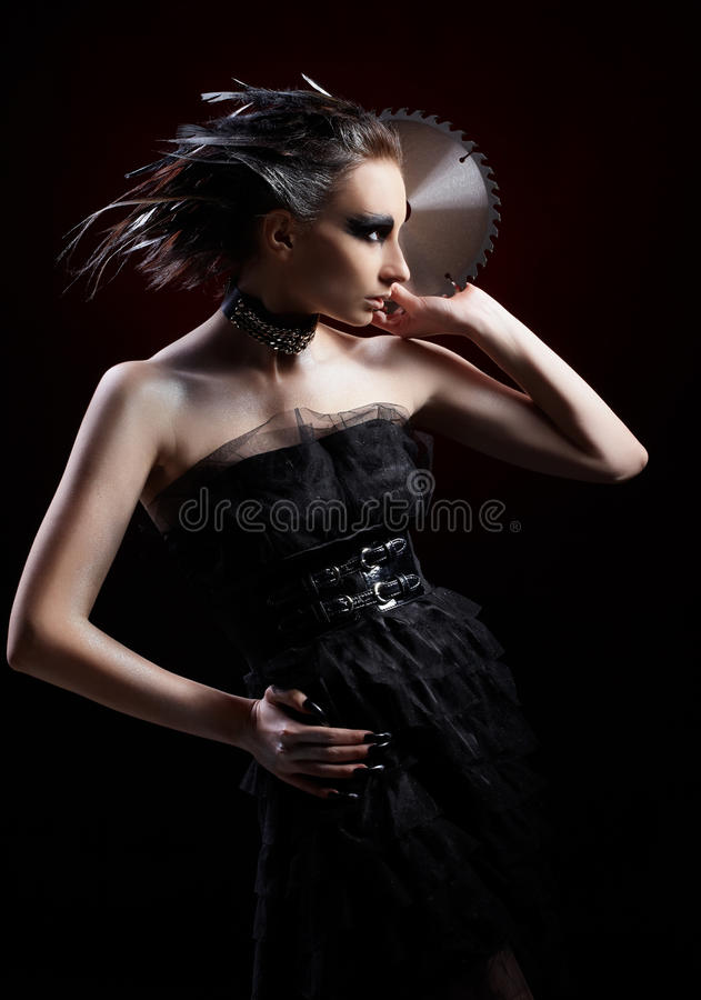 Girl with circular saw. Portrait of beautiful girl with bird of prey fantasy make-up with circular saw blade royalty free stock photography