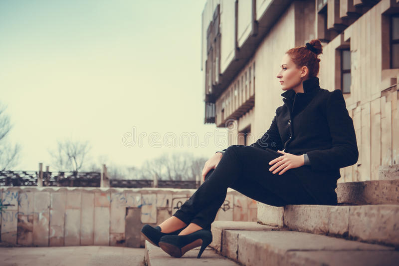 Girl city portrait. Portrait of red-haired girl on the background of the urban city stock images