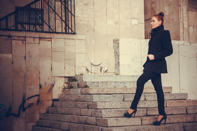 Girl city portrait. Girl on the steps of a building on the background of the city royalty free stock images