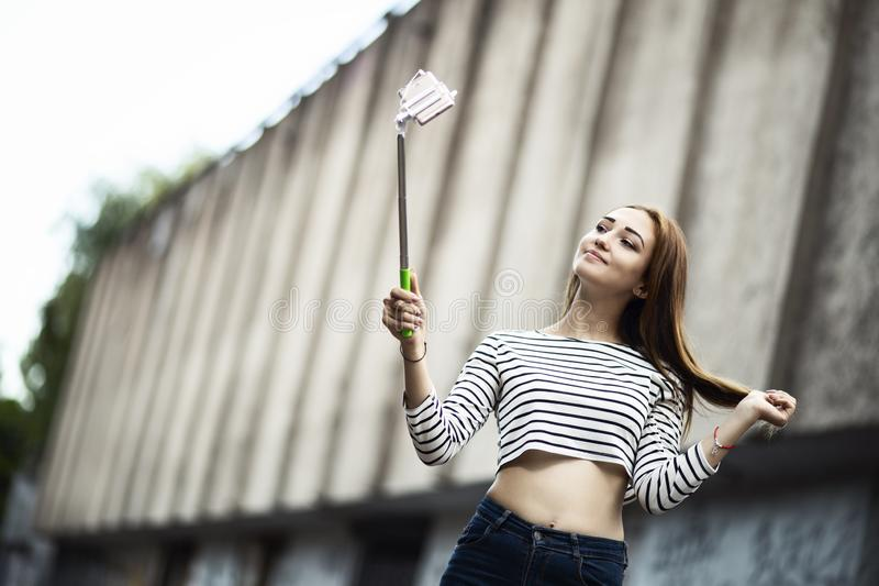 Girl in a city posing to smartphone, young woman making selfie for social network, concept teenager lifestyle stock photography