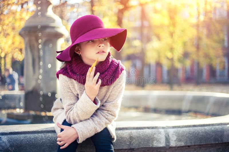 Girl in classic coat and hat in autumn park near the fountain. Autumn season, fashion, childhood stock image