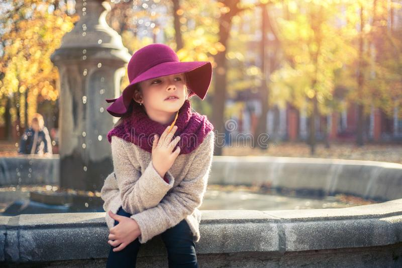 Girl in classic coat and hat in autumn park near the fountain. Autumn season, fashion, childhood royalty free stock image