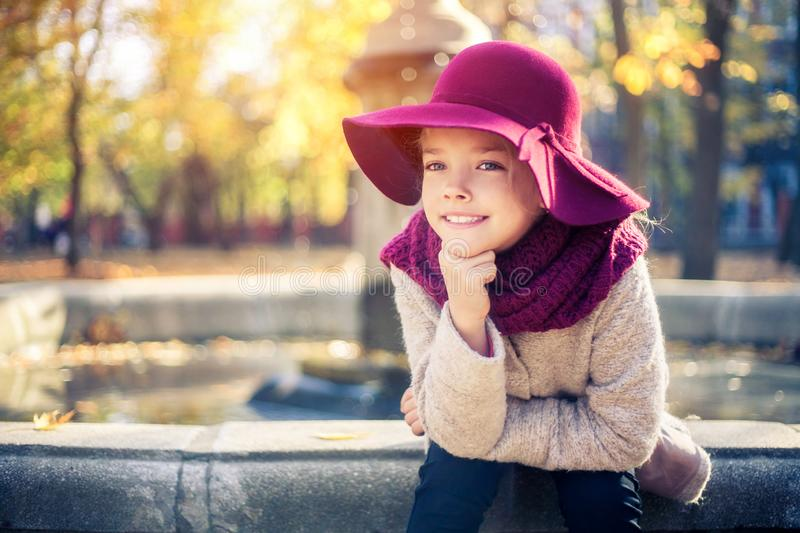 Girl in classic coat and hat in autumn park near the fountain. Autumn season, fashion, childhood stock photography