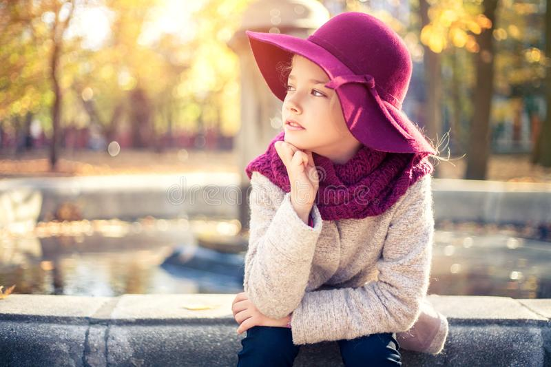 Girl in classic coat and hat in autumn park near the fountain. Autumn season, fashion, childhood royalty free stock photos