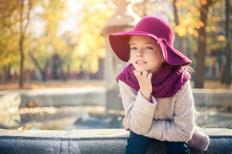 Girl in classic coat and hat in autumn park near the fountain. Autumn season, fashion, childhood royalty free stock photography