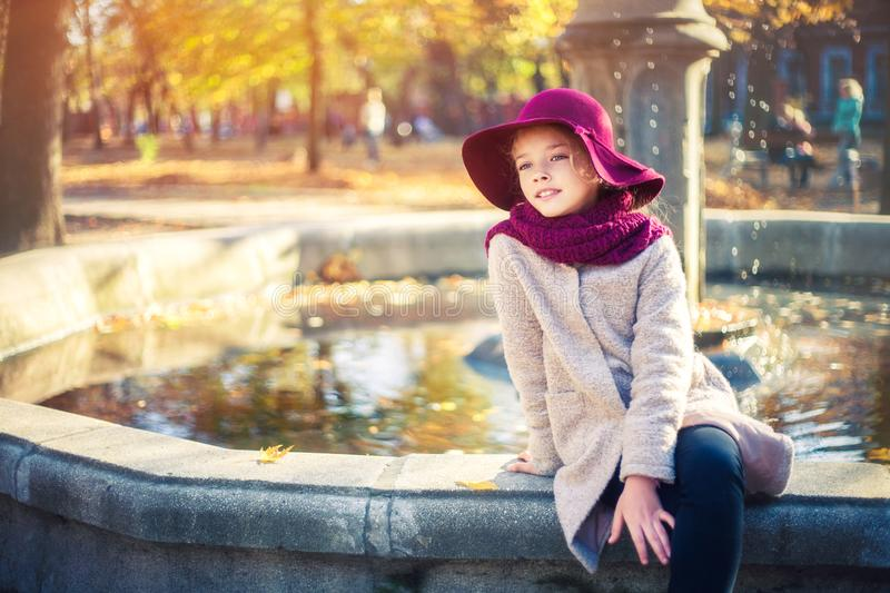 Girl in classic coat and hat in autumn park near the fountain. Autumn season, fashion, childhood stock photos