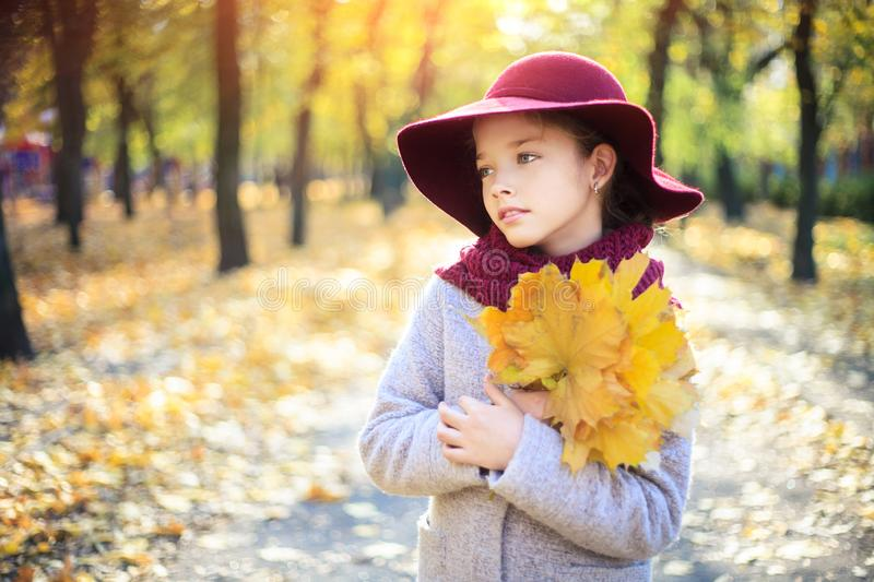 Girl in classic coat and hat in autumn park. Autumn season, fashion, childhood stock images