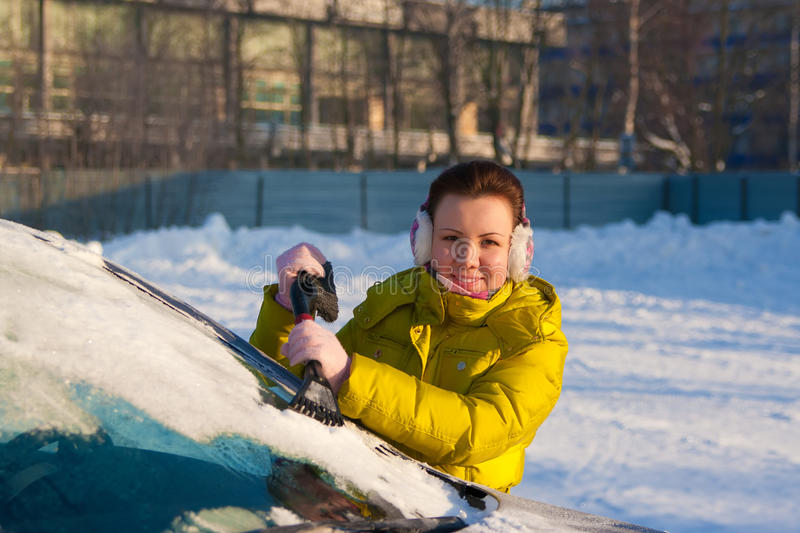 Girl cleaning car from snow stock photography