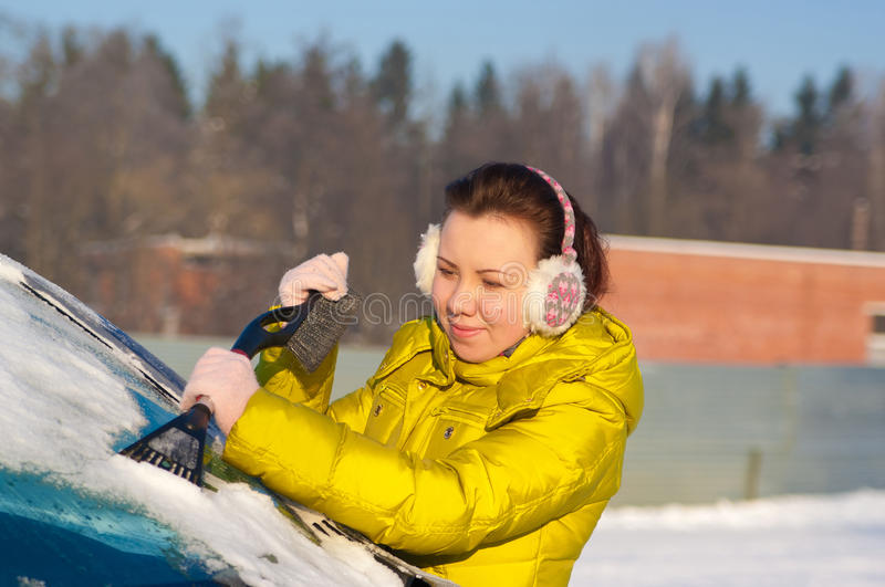 Girl cleaning car from snow royalty free stock image