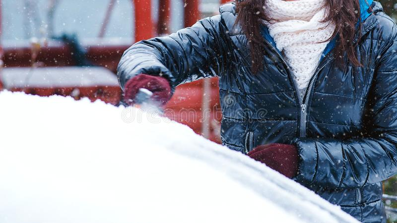 Girl cleaning car from snow. Clean car window from snow. Winter windshield car cleaning. Removing snow from window.  royalty free stock photos