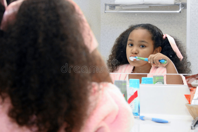 Girl cleaning teeth. Cute young girl cleaning her teeth, reflected in mirror stock photos