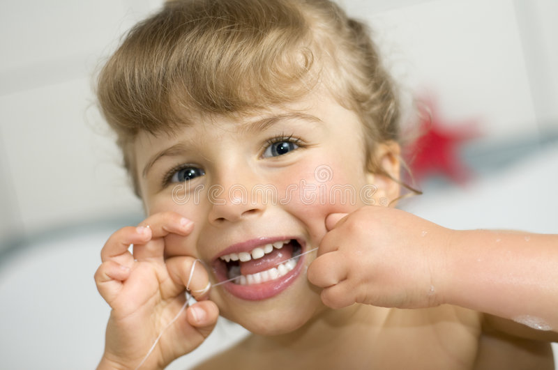 Girl cleaning teeth by dental floss royalty free stock photo
