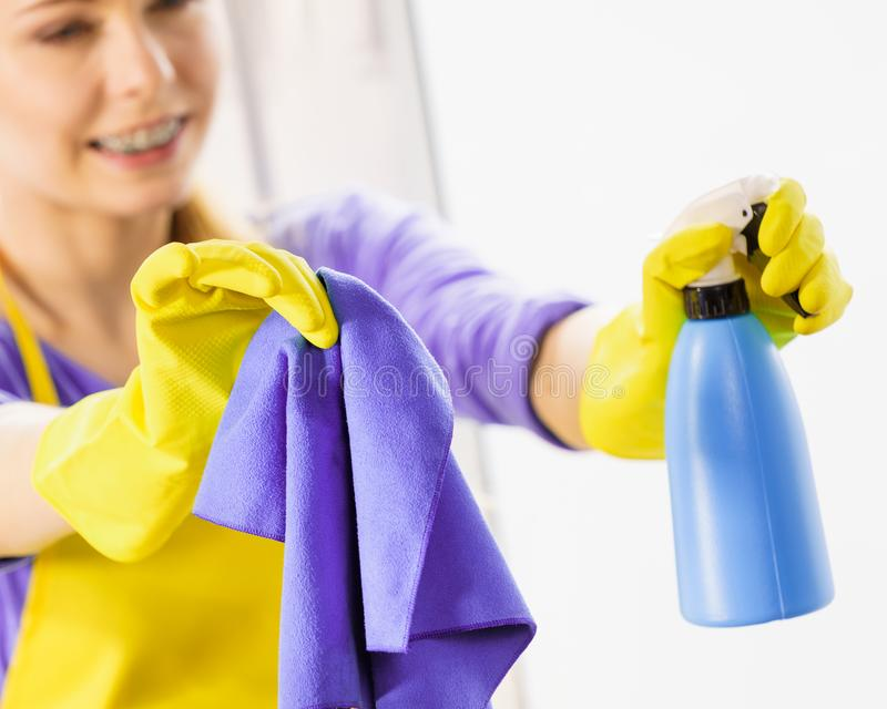 Girl cleaning window at home royalty free stock image