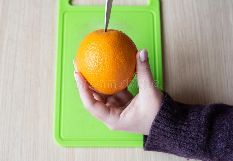 Girl cleans the orange with a knife. Healthy food stock images