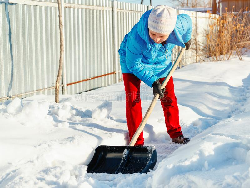 Girl cleans snow shovel on the site near his house. sunlight stock images