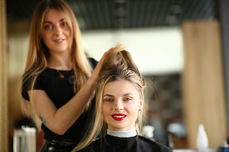 Girl Client Getting Hairstyle by Hairdresser. Hairstylist Holding Hair of Female Customer for Styling New Haircut. Young Beautician Styling Hairdo for Woman royalty free stock photography