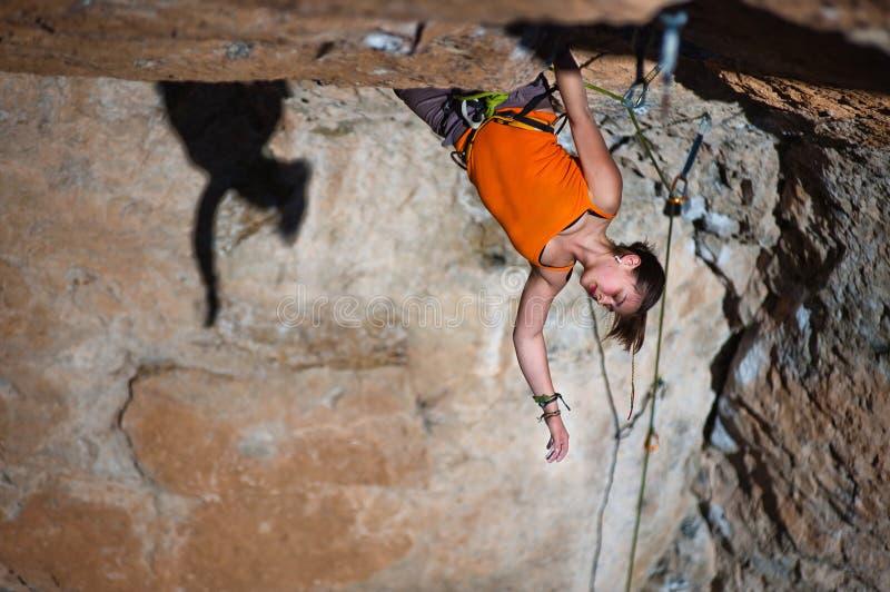 Girl climber climbs on rock. stock photos