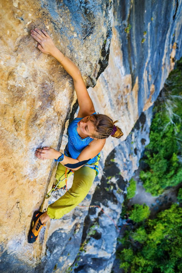 Girl climber climbs on rock. stock images