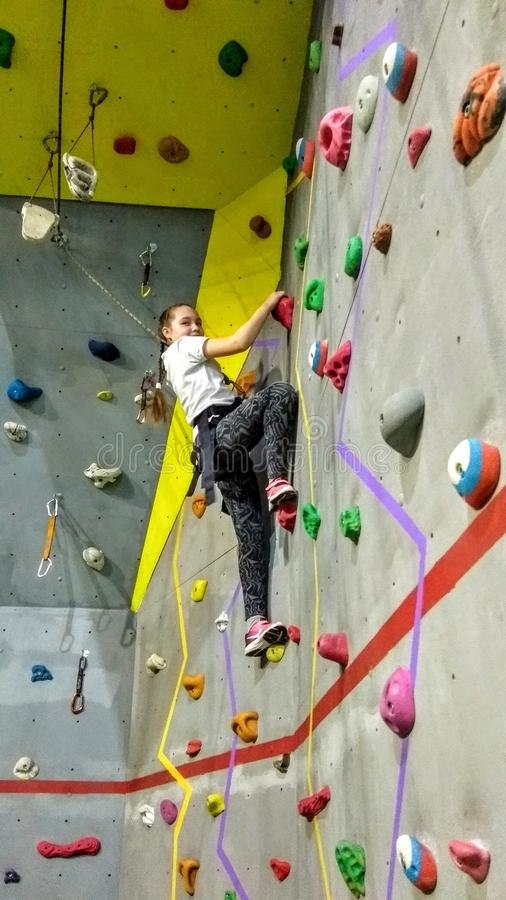 Girl climber in a training pavilion climbing wall. Girl mountaineer in the training pavilion climbing gym physical training of children and adolescents royalty free stock photography