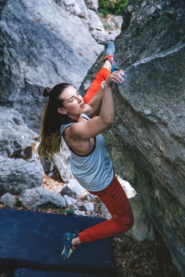 Girl climbing boulder. royalty free stock photo