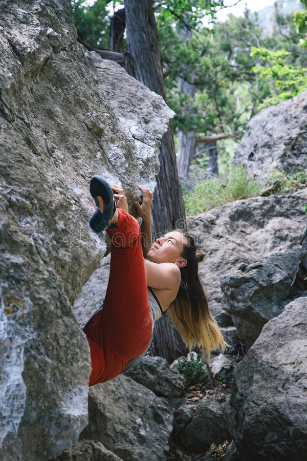 Girl climbing boulder stock photos