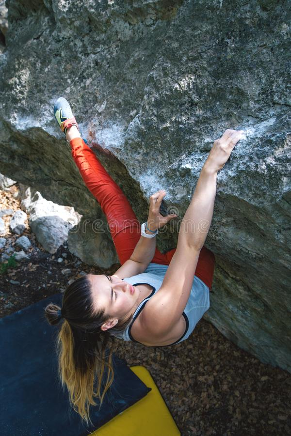 Girl climbing boulder. royalty free stock image