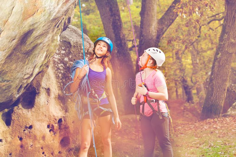 Girl and climbing coach at the foot of a mountain stock photo