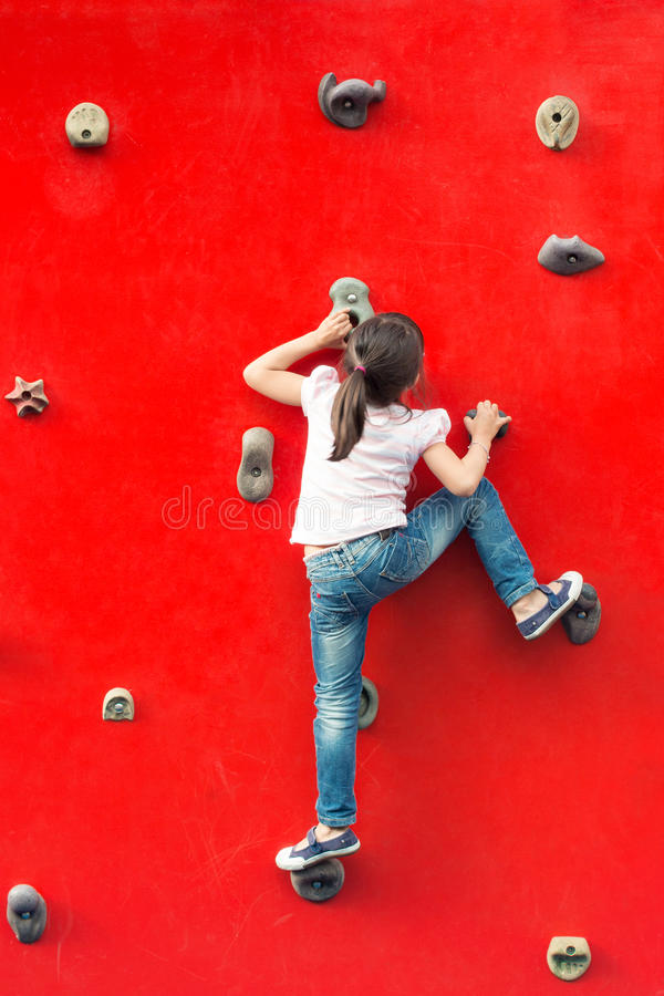 Girl climbing a wall in a playground stock images