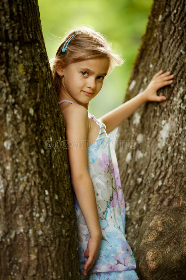 Girl climbs big tree in park royalty free stock photography