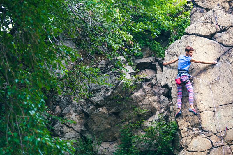 The girl climbs the granite rock royalty free stock photo