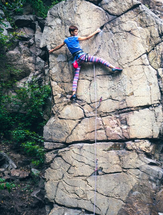 The girl climbs the granite rock royalty free stock photos