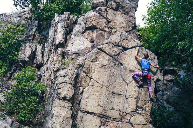 The girl climbs the granite rock stock images