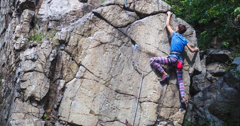 The girl climbs the granite rock stock image