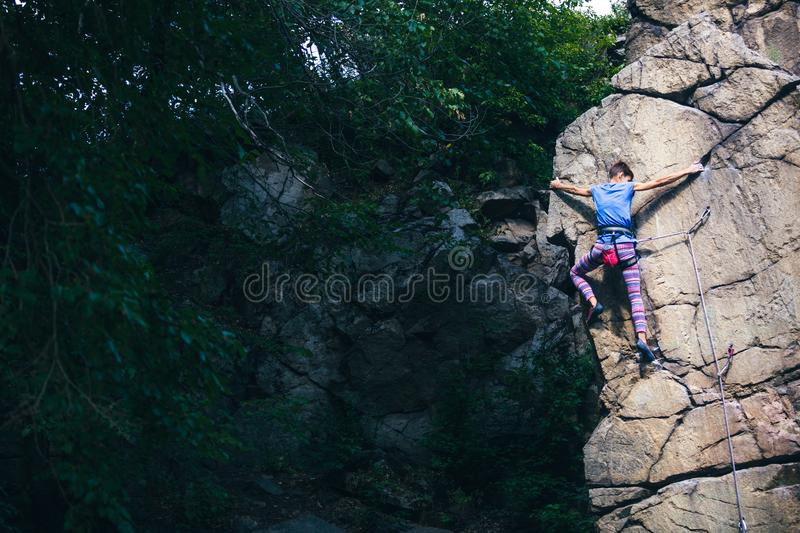 The girl climbs the granite rock stock photography