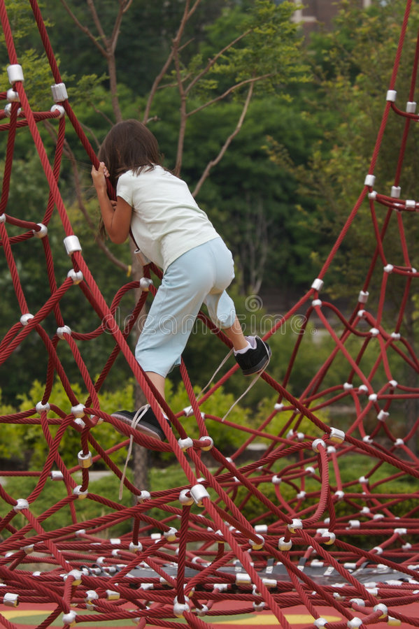 Girl Climbs Red Ropes. Girl with shoes untied navigates a spider-like large playground set made of thousands of red ropes interconnected between four tall black royalty free stock images