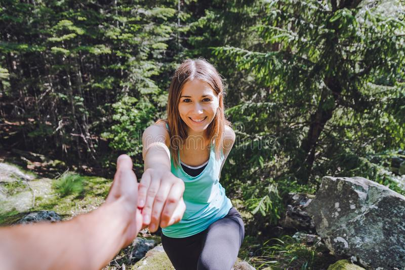 Girl climbs on rock, partner pulls out hand for assistance stock photography