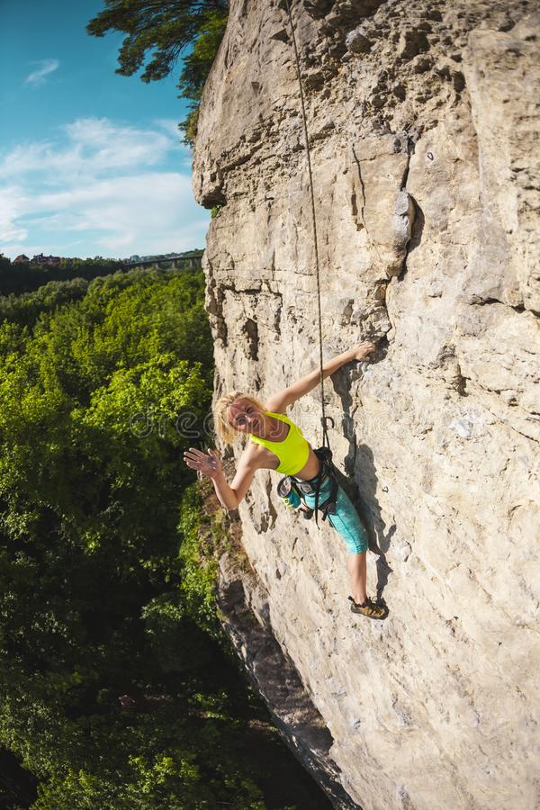 The woman gives five. The girl climbs the rock. A woman is engaged in fitness in nature. The climber gives five companions after overcoming the climbing route royalty free stock images
